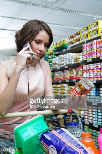 Young woman in supermarket, pushing shopping trolley, using mobile phone : Stock Photo