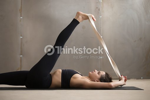 Young woman in Supta Padangushthasana pose, grey studio backgrou : Stock Photo