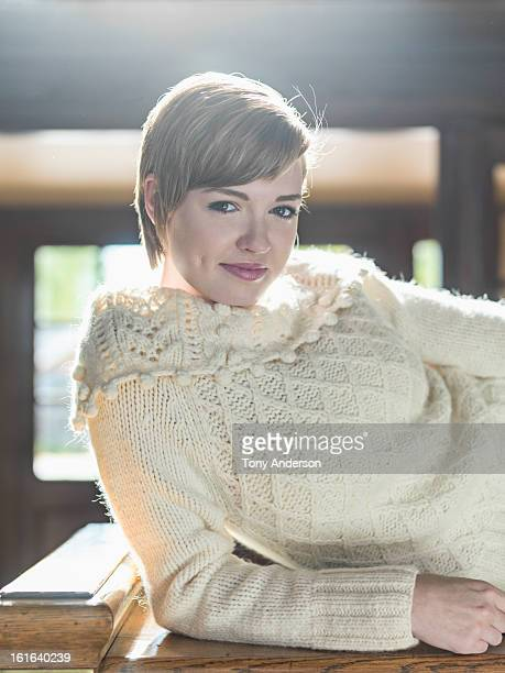 Young woman in sweater reclining on bench