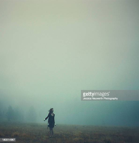 Young woman in sweater standing in misty field