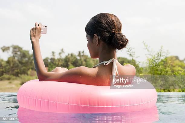 Jeune femme dans la piscine avec un appareil photo