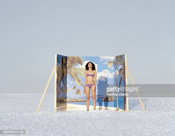 Young woman in swimsuit standing in front of backdrop with snow