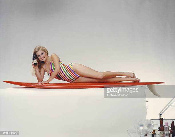 Young woman in swimwear lying on surfboard with beer bottle, portrait