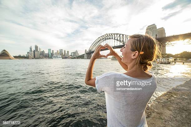 Young woman in Sydney harbour makes heart shape finger frame
