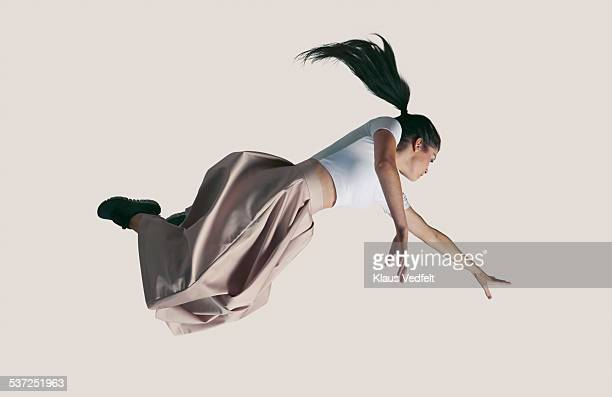Young woman in the air strecthing arm to reach out