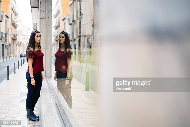 Young woman in the city looking in shop window