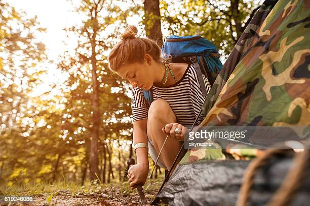 Young woman in the forest setting up camp tent.