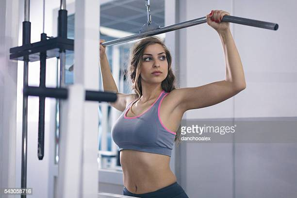 Young woman in the gym lifting weights