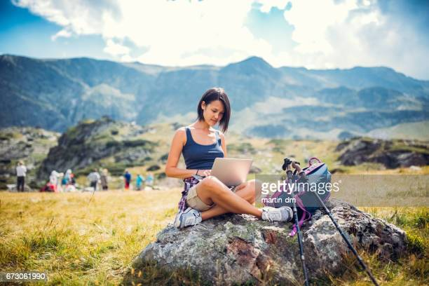Young woman in the mountain using lap top