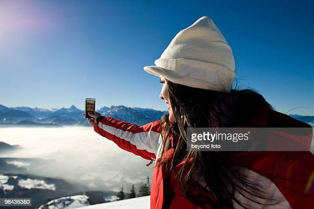 young woman in the mountains taking picture with camera phone