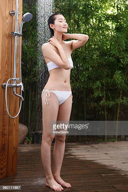 A young woman in the outdoor shower