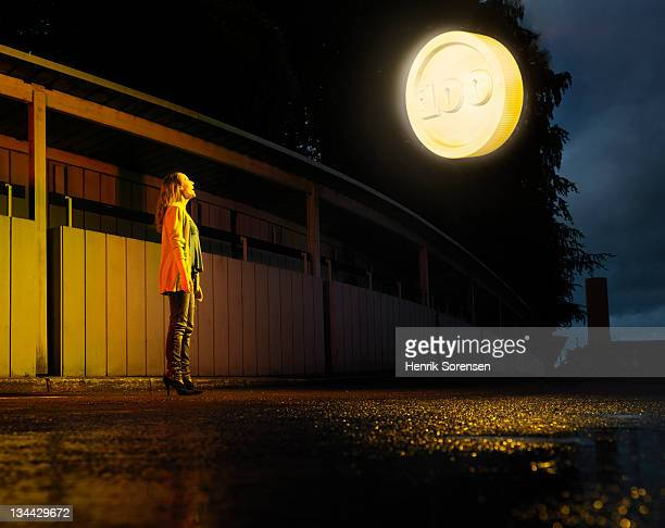 young woman in the street lookin at giant coin