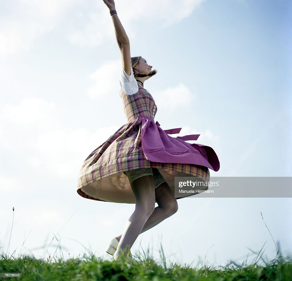 young woman in traditional Bavarian dress dancing with lifted skirt