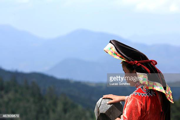 A young woman in traditional clothes in a valley on May 3 2007 near Lijiang Yunnan province China