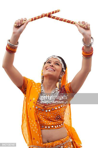 Young woman in traditional wear performing Dandiya Raas over white background