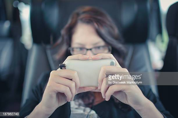 Young woman in train with mobile device