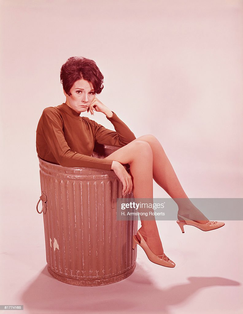 Young woman in trash can with legs hanging out. (Photo by H. Armstrong Roberts/Retrofile/Getty Images) : Stock Photo