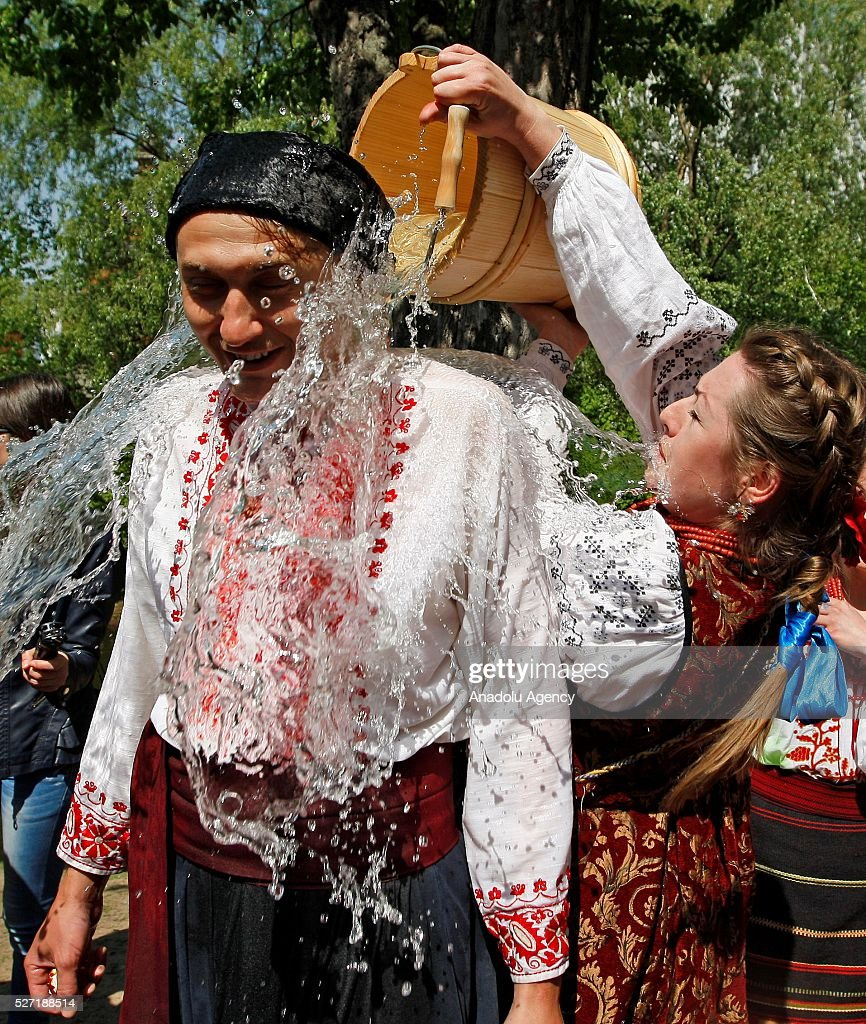 Young woman in Ukrainian traditional clothe pour water on a man during folk Easter Tradition of pouring water called 'Pouring Monday' in open air Cossack village 'Mamaeva Sloboda', Ukraine,on May 02, 2016. The tradition of pouring water when single guys pour unmarried girls by water is celebrated on the first Monday after Orthodox Easter.
