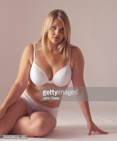 Young woman in underwear, sitting on floor, portrait