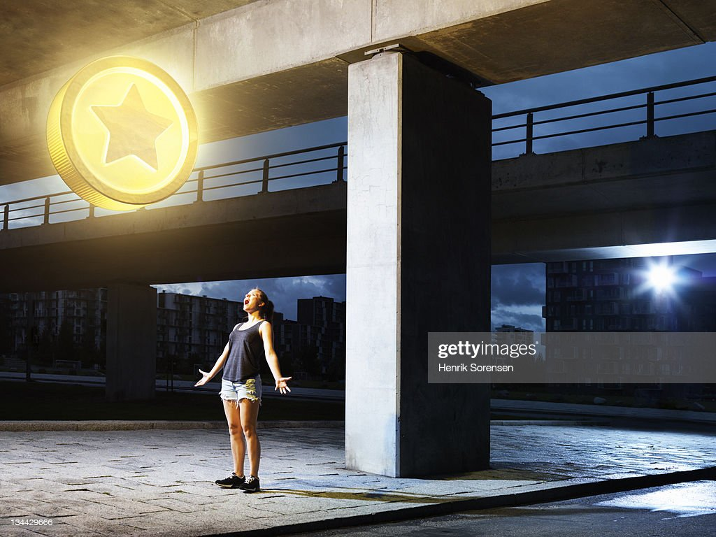 young woman in urban  environment looking at coin