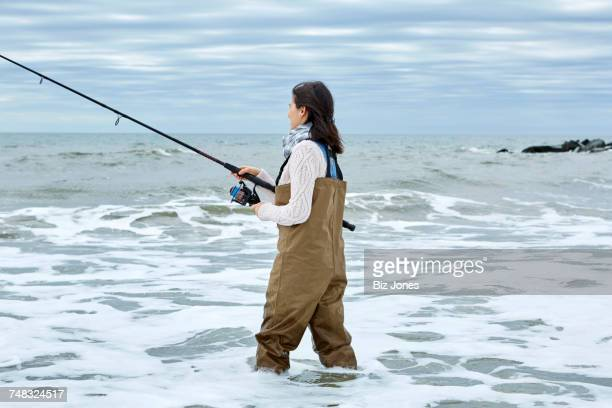 Young woman in waders sea fishing knee deep in water