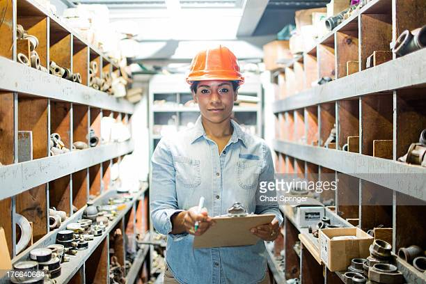 Young woman in warehouse with clipboard
