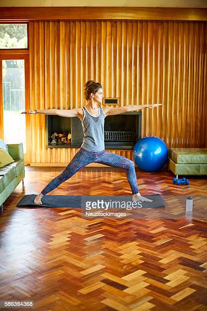 Young woman in warrior yoga position in living room