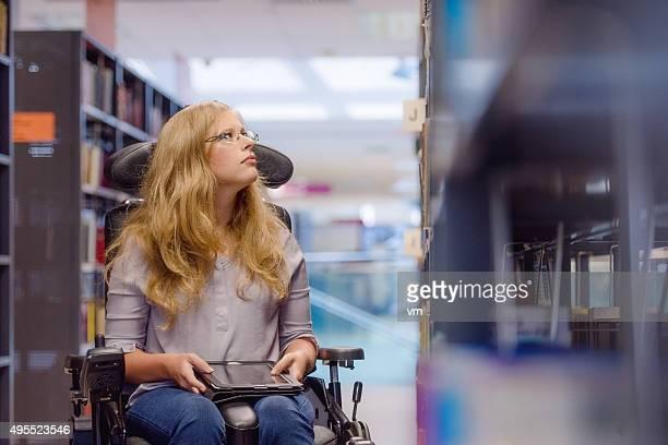 Junge Frau in wealchair in der Bibliothek