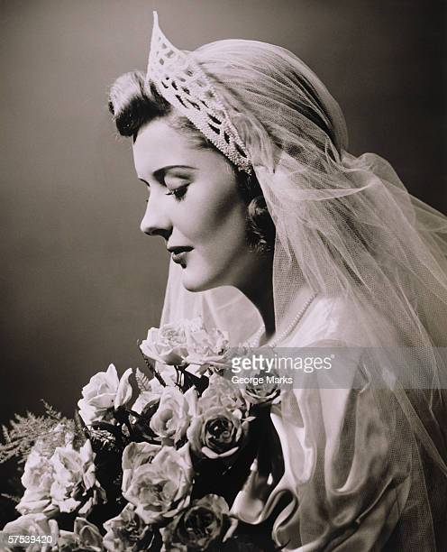 Young woman in wedding dress and bouquet in studio, (B&W), close-up