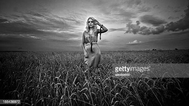 Giovane donna in un campo di grano al tramonto