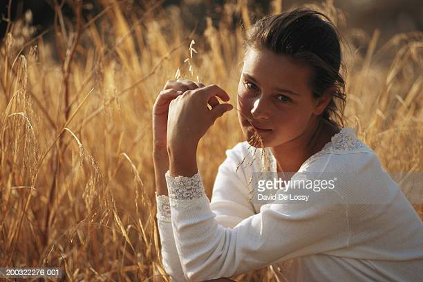 Young woman in wheat field, smiling, portrait