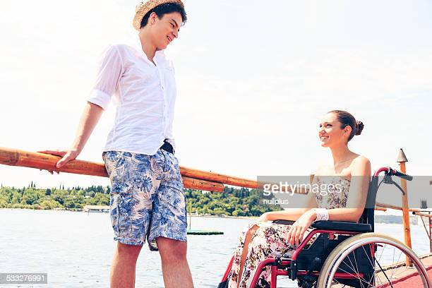 young woman in wheelchair by the sea