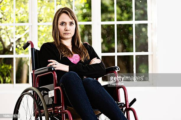Young woman in wheelchair frowns unhappily