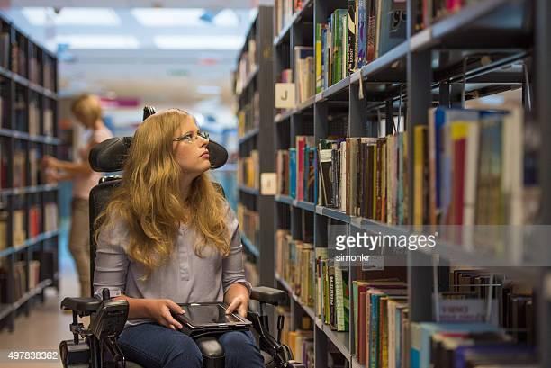 Giovane donna in sedia a rotelle in biblioteca