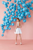 Young woman in white cocktail dress standing back to camera on pink wall background with blue bubbles hanging. Dreaming concept