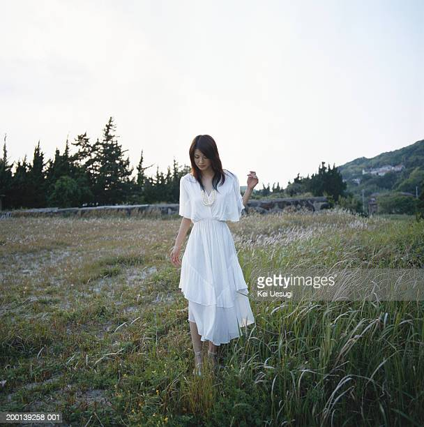 Young woman in white dress, walking through field