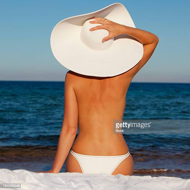 Young woman in white sun hat relaxing on beach