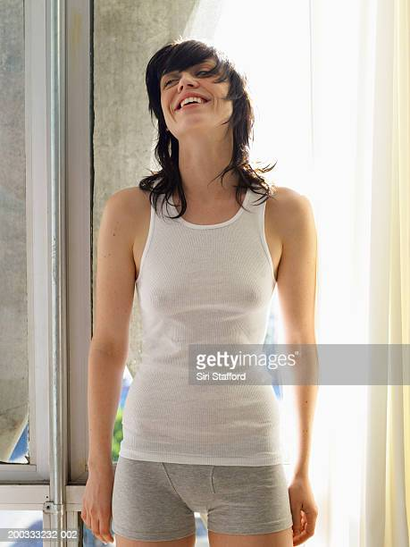 Young woman in white tank top and boxer briefs standing by window