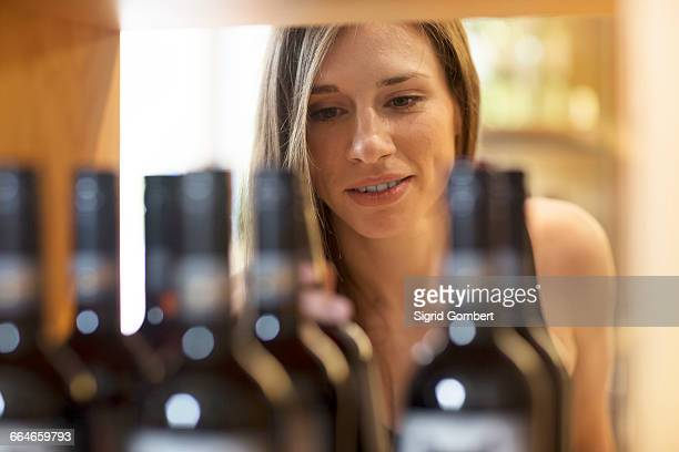 Young woman in wine shop choosing bottle of wine