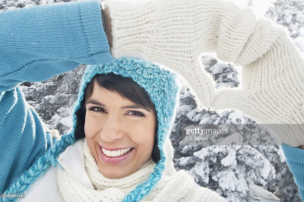 Young woman in winter clothes making heart shape with hands : Stock Photo