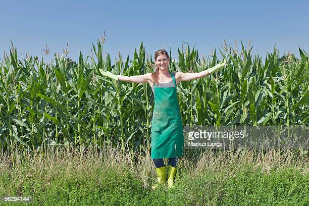 Young woman in work clothes standing with outstretched arms in front of a maize field, Baden-Wurttemberg, Germany