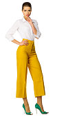 Young woman in yellow pants isolated