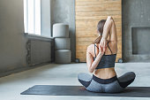 Slim woman in yoga class making asana exercises. Girl do back and shoulders stretching. Healthy lifestyle in fitness club.