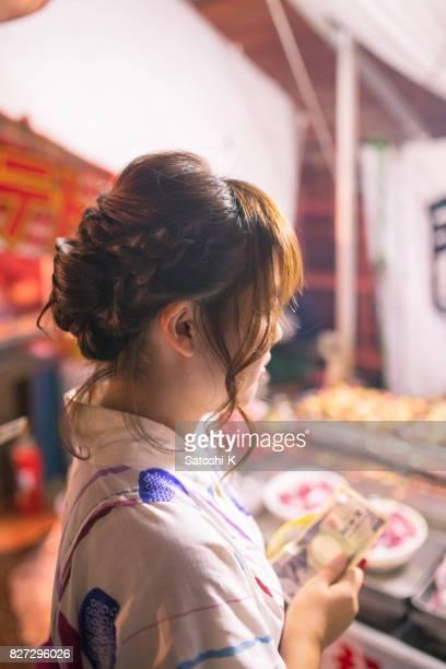 浴衣花火大会でたこ焼きを買っての若い女性