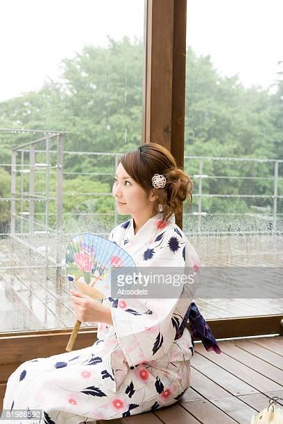 Young woman in yukata sitting near window
