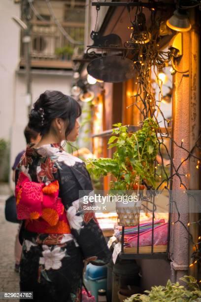 Young woman in yukata walking in traditional shopping street