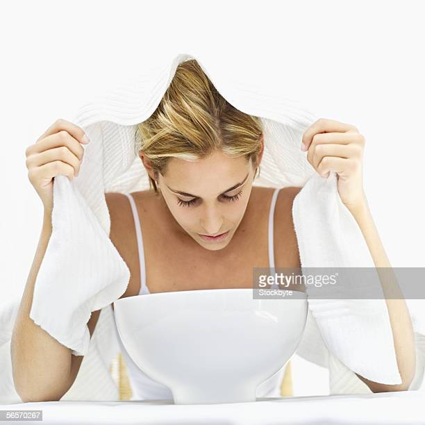 young woman inhaling steam from a basin with a towel on her head