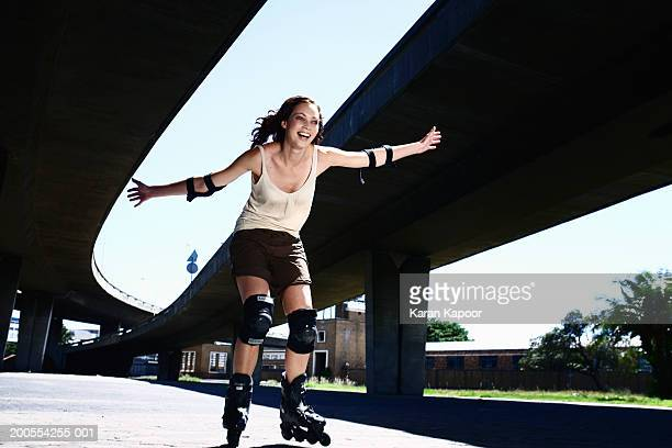 Young woman inline skating, smiling, low angle view