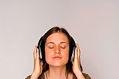 Young woman intently listening to music on headphones.