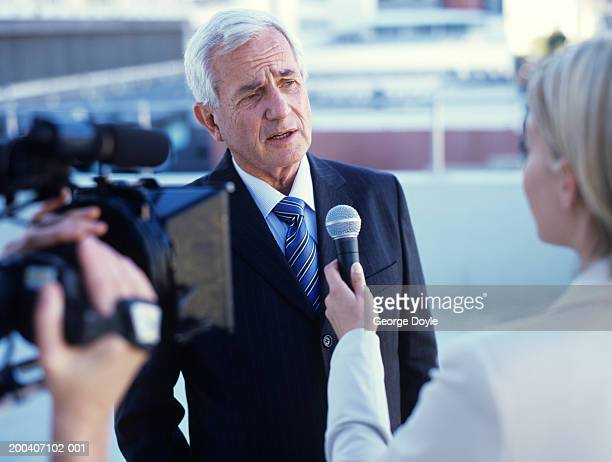 Young woman interviewing senior man